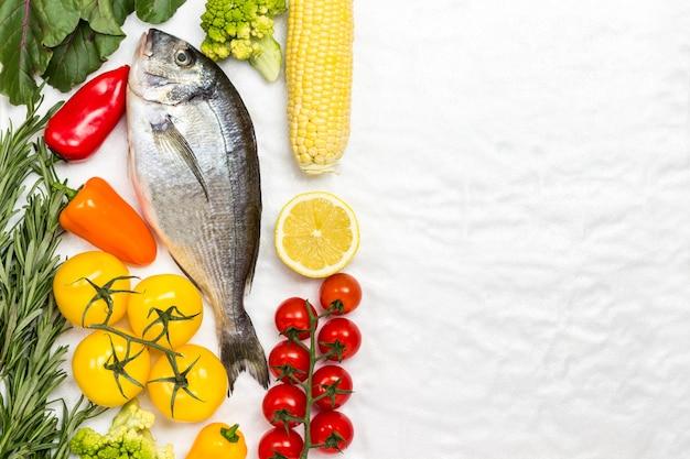 Pesce fresco di dorado con verdure e vegetazione.
