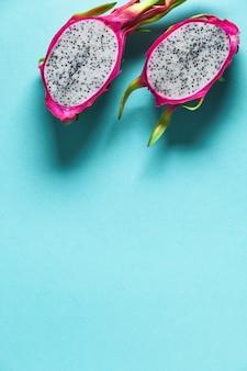 Dragonfruit fresco, pitaya o pitahaya, tagliato a metà su sfondo blu menta. layout piatto creativo con copia-spazio, posto per il testo. frutto esotico alla moda dai vivaci colori rosa e verde.