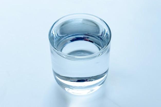 Bere acqua fresca in vetro con sfondo bianco