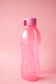 Acqua potabile fresca in una bottiglia di colore rosa