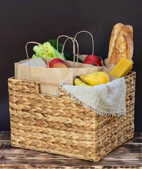 Verdure, verdure e frutta organiche fresche di eco, cereali e pasta in un cestino di vimini. consegna o donazione del concetto di cibo di fattoria ecologica