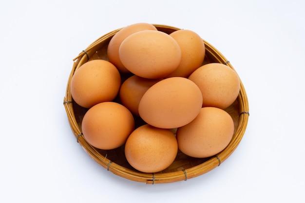 Uova fresche in cesto di bambù su sfondo bianco. copia spazio