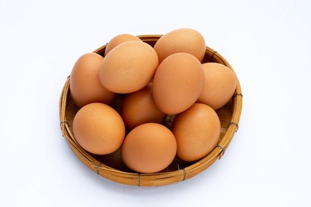 Uova fresche in cestino di bambù su superficie bianca.