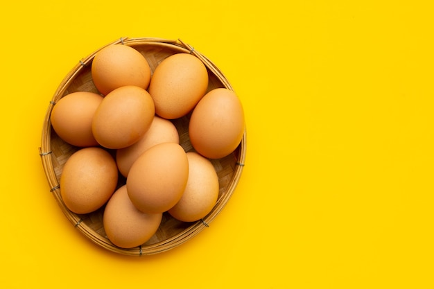 Uova fresche in cesto di bambù su sfondo giallo. copia spazio