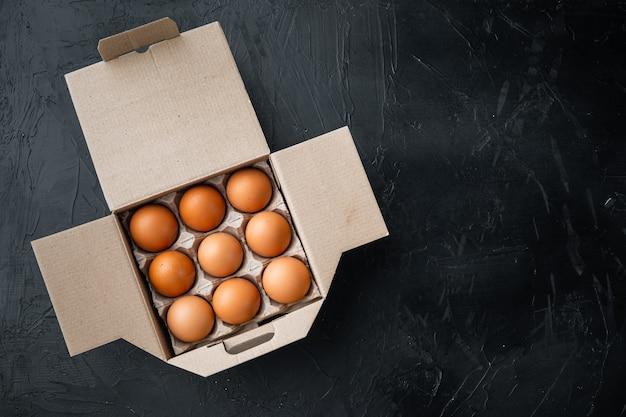 Uova fresche sul set di scatole per uova di carta, su sfondo nero, vista dall'alto laici piana, con spazio per il testo copyspace