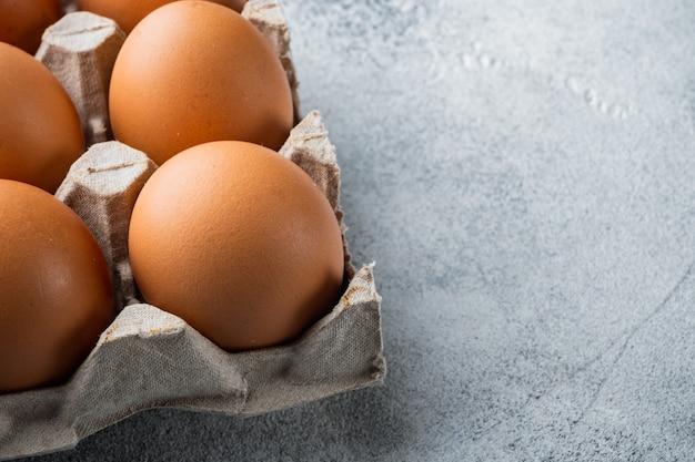 Uova fresche sulla scatola delle uova di carta impostata su sfondo grigio, con spazio per il testo copyspace