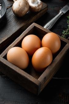Uova fresche sul set di scatole per uova di carta, sul vecchio fondo di tavola in legno scuro