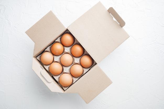 Uova fresche su carta scatola portauova, su bianco