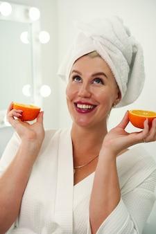 Energia fresca, felice, allegra, graziosa, donna, sorridente, con, denti bianchi, presa a terra, due metà di un'arancia e...