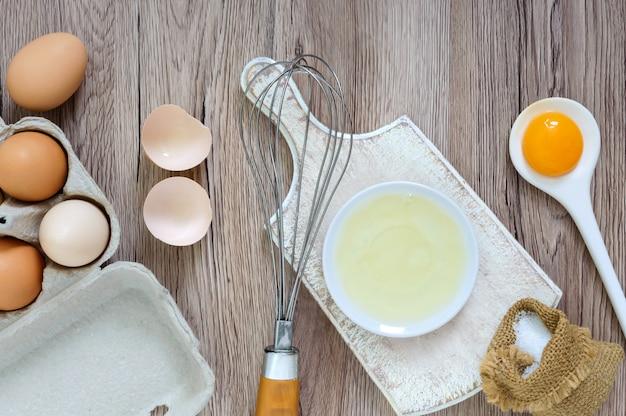 Uova fresche dell'azienda agricola su un fondo rustico di legno. albume e tuorli separati, gusci d'uovo rotti. sbattere le uova con la frusta.