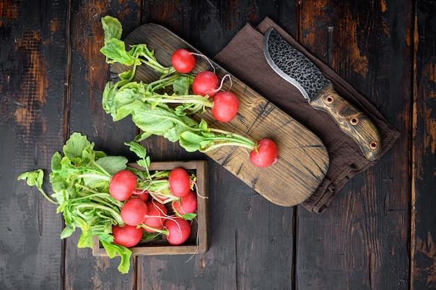 Ravanello fresco dell'azienda agricola, fondo rustico. set di prodotti ecologici naturali, su un vecchio tavolo in legno scuro