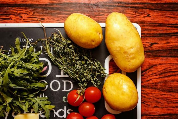Frutta fresca e verdura del mercato degli agricoltori con formaggio sulla tavola rossa