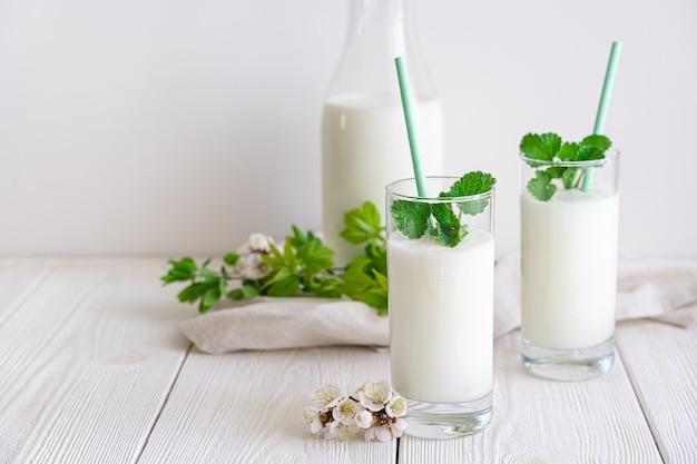 Bevanda refrigerata di latte fresco fermentato lassi in due bicchieri su una parete bianca con vegetazione e fiori. vista laterale, copia dello spazio.
