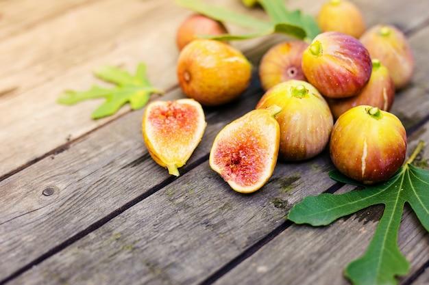 Fichi freschi tagliati a metà con fichi interi sullo sfondo, su una superficie di legno. frutti di fico su un piatto di legno.