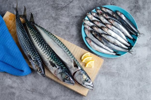 Pesce fresco sul piatto blu sulla superficie di marmo. copia spazio. vista dall'alto.