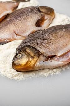 Carassiere di pesce fresco con sale grosso. cucinando, da vicino. copia spazio