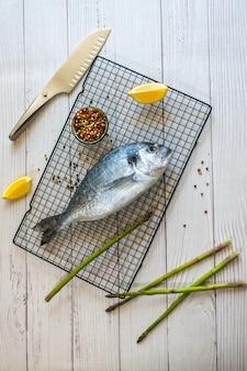 Un pesce fresco su una griglia circondato dal limone