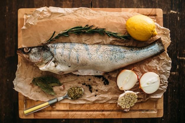Ingredienti per la preparazione di pesce fresco, erbe aromatiche, spezie, cipolla e aglio, limone sul tagliere ricoperto di carta pergamena, vista dall'alto