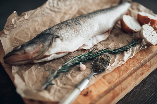 Preparazione di pesce fresco, rosmarino, spezie, cipolla e aglio sul tagliere ricoperto di carta pergamena, vista del primo piano