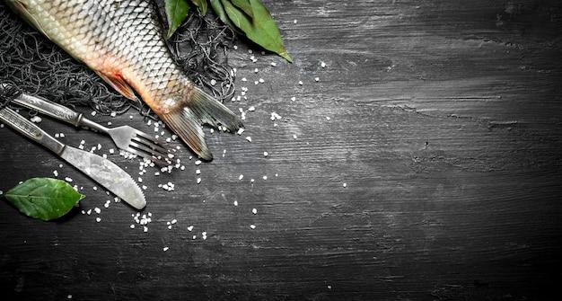 Pesce fresco con rami di alloro sulla rete da pesca. su uno sfondo di legno nero.
