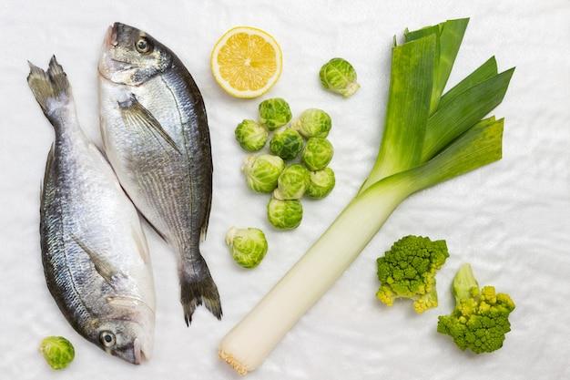 Pesce fresco con verdure verdi.