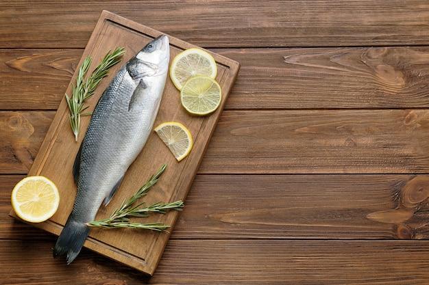 Pesce fresco con rosmarino e fettine di limone su tavola di legno
