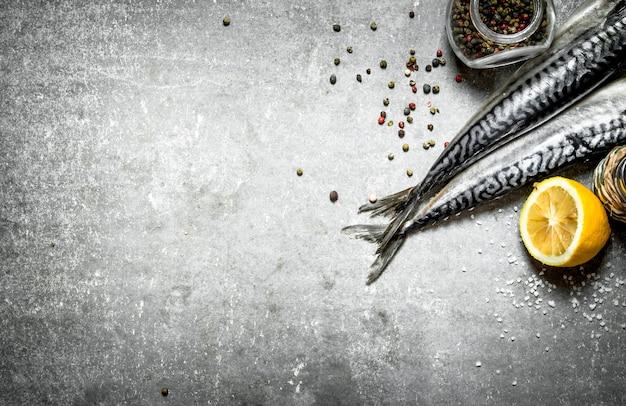 Pesce fresco con spezie e limone sul tavolo di pietra.