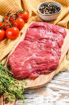 Bistecca di fianco fresca su un tagliere. sfondo bianco. vista dall'alto.