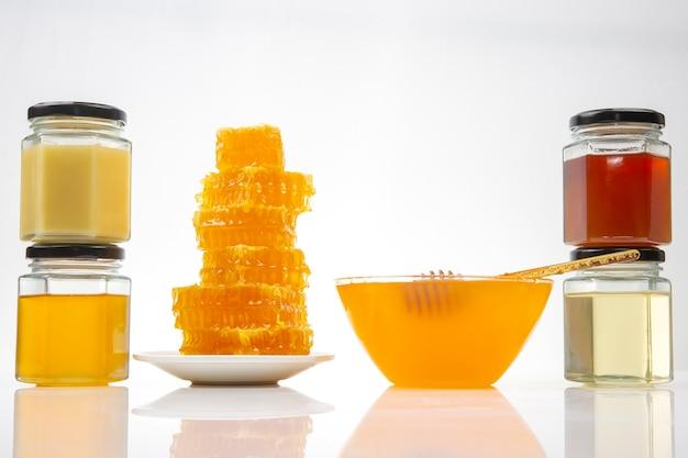 Miele di fiori freschi di diverse varietà e a nido d'ape con cucchiai su uno sfondo di legno. cibo salutare con vitamine organiche