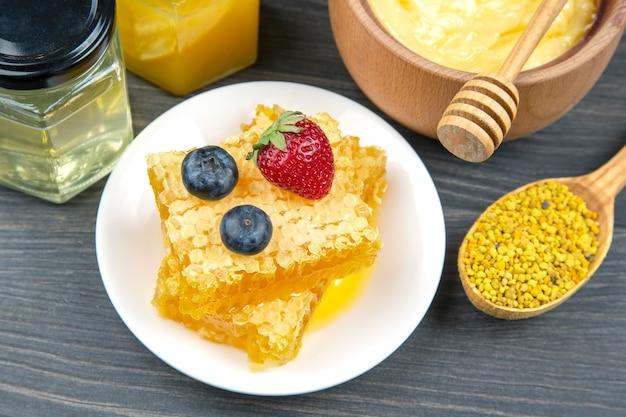 Miele di fiori freschi di diverse varietà, polline e favo con cucchiai su fondo di legno. cibo salutare con vitamine organiche