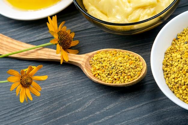 Miele di fiori freschi di diverse varietà, polline con cucchiai su uno sfondo di legno. cibo salutare con vitamine organiche