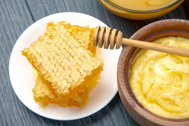 Miele di fiori freschi e nido d'ape con cucchiai su uno sfondo di legno. cibo salutare con vitamine organiche