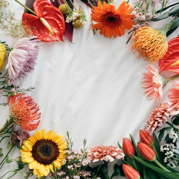 Cornice rotonda di fiori freschi su sfondo bianco