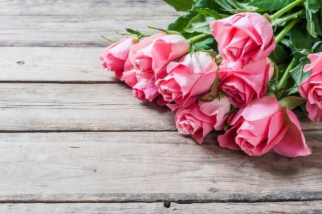 Fiori freschi sulla parete in legno, bordo del fiore, parete floreale con posto per il testo