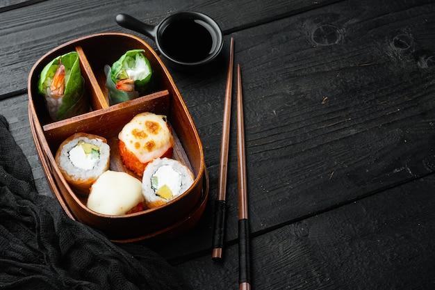 Porzione di cibo fresco in giapponese bento box con sushi rolls impostato, nero sul tavolo di legno