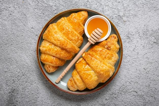 Croissant francesi freschi con cioccolato sulla piastra, miele su sfondo grigio granito continental