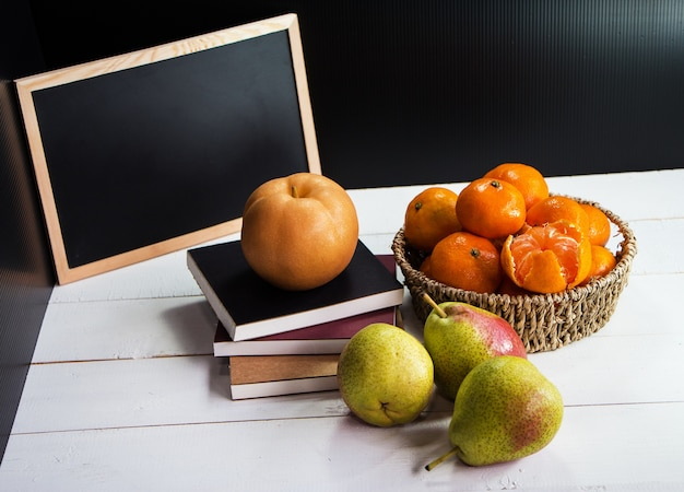 Il frutto fresco, pera messo su libri impilati, gruppo di arance inserite nel cesto intrecciato,