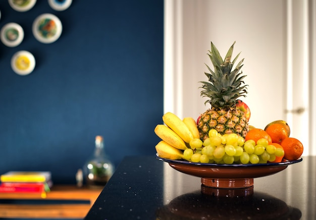 Ciotola di frutta fresca in interni moderni vicino al muro blu scuro in cucina, bella casa dal design moderno. banane ananas e frutta varia