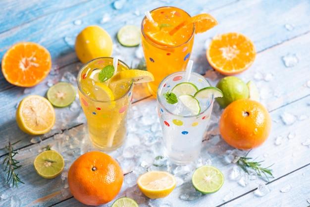 Frutta fresca su ghiaccio cocktail tè fatto in casa con mojito limone lime arancia rosmarino e foglia di menta, bevanda estiva colorata succosa, bevande estive esotiche rinfrescanti varietà di bicchieri di bevande fredde