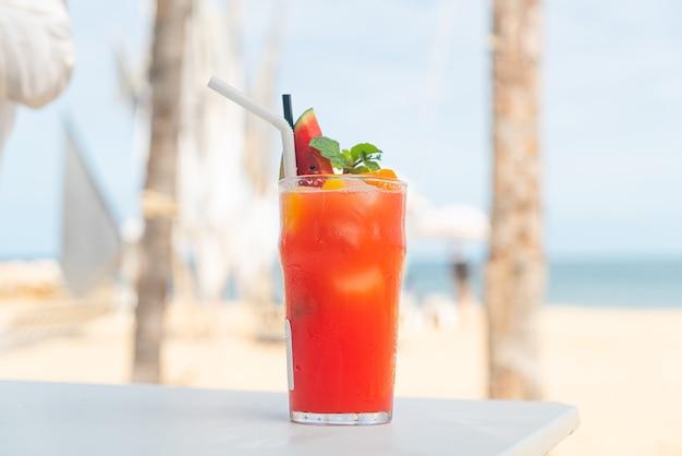 Punch alla frutta fresca con sfondo di spiaggia di mare