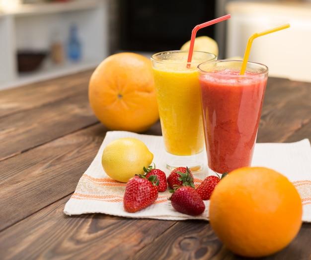 Frullati di frutta fresca sul tavolo della cucina in due bicchieri
