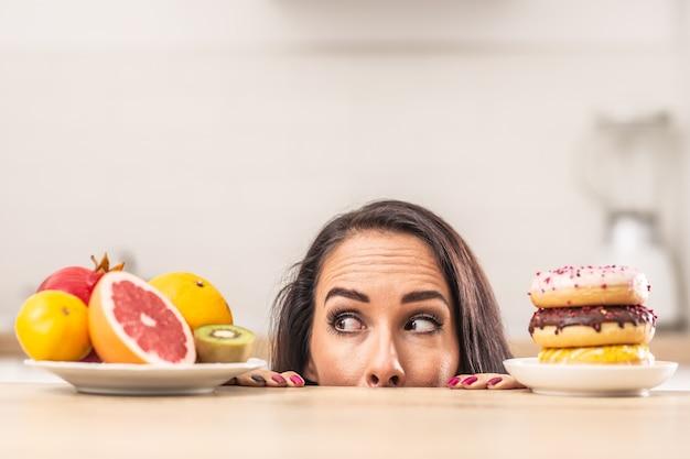 Preferenza di frutta fresca su ciambelle malsane da parte di una donna in cucina.
