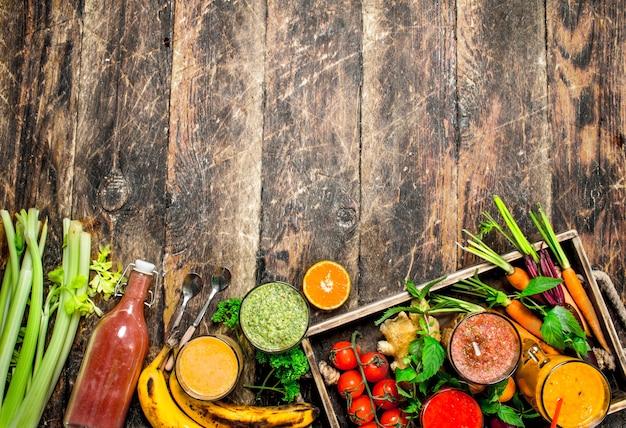 Frullati di frutta fresca, verdura e frutti di bosco. su uno sfondo di legno.