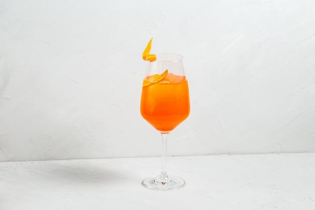 Cocktail dell'alcool di giallo della frutta fresca in bicchiere di vino