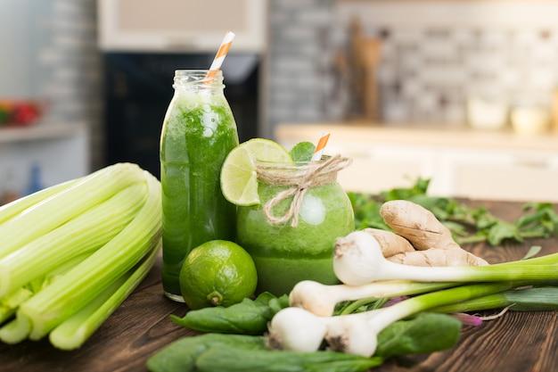 Frutta fresca e bottiglia con frullati verdi sul tavolo della cucina