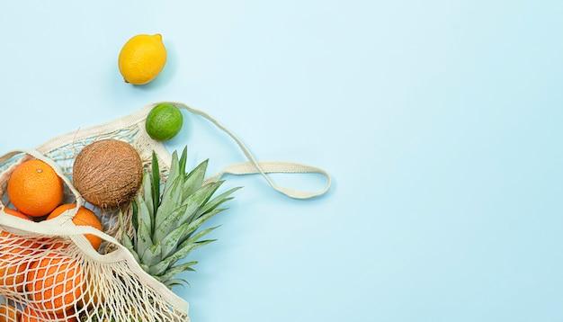Frutta fresca in un sacchetto a rete su sfondo azzurro