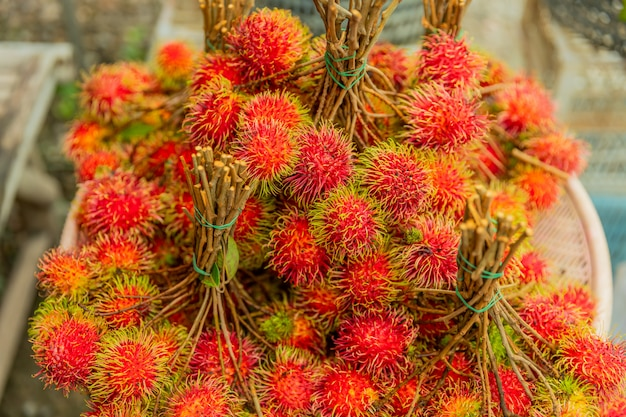 Sfondo di rambutan di frutta fresca, rambutan rosso e rambutan giallo in un mercato locale,