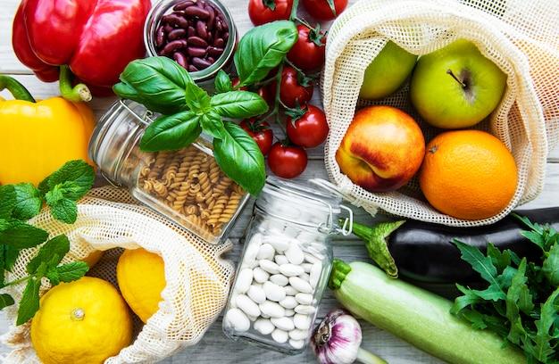 Frutta e verdura fresca in sacchetti di cotone eco sul tavolo in cucina.