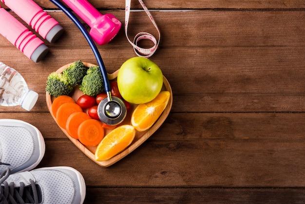 Frutta fresca e verdura in legno piatto cuore e attrezzature sportive e stetoscopio medico