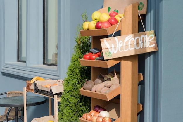 Frutta fresca e verdura sul bancone del mercato con cartello di benvenuto. mercato locale, prodotti dell'orto, cibo pulito e concetto di dieta. mercato degli agricoltori, alimenti biologici, selezione di cibi sani.